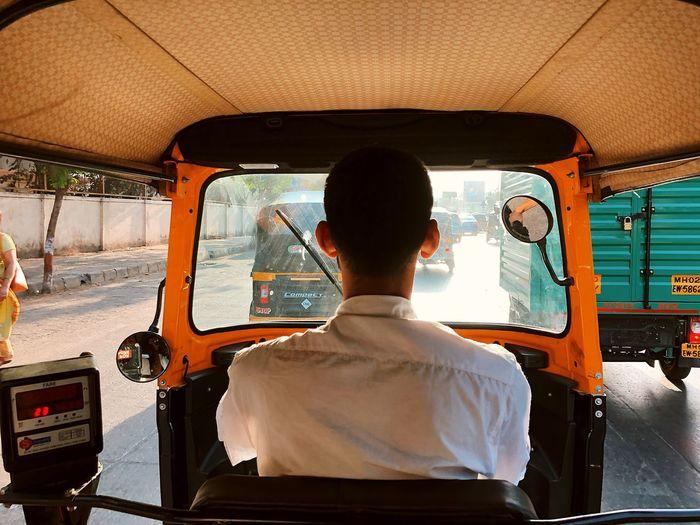 Rear view of man riding auto rickshaw