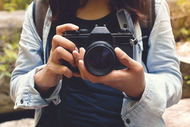 Camera - Photographic Equipment Close-up Day Front View Holding Lifestyles Outdoors Photographer Photography Themes Real People Technology