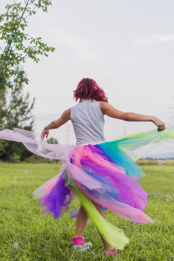 Rear View Of Woman Dancing On Field Against Trees