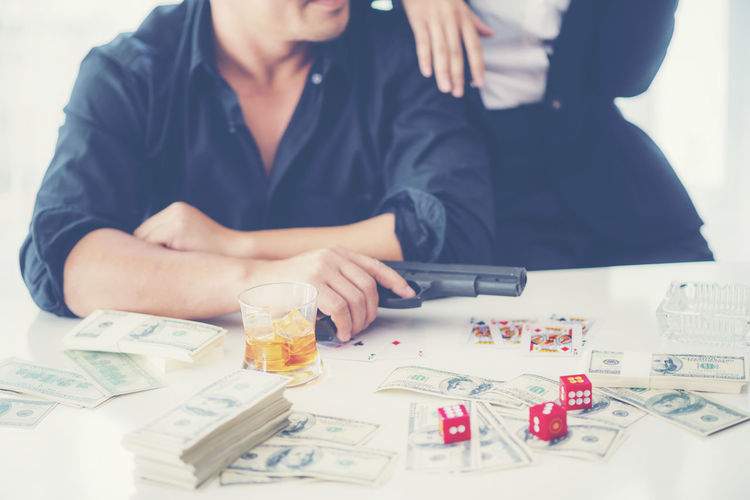 Portrait of businesswoman gambling while sitting on table at office