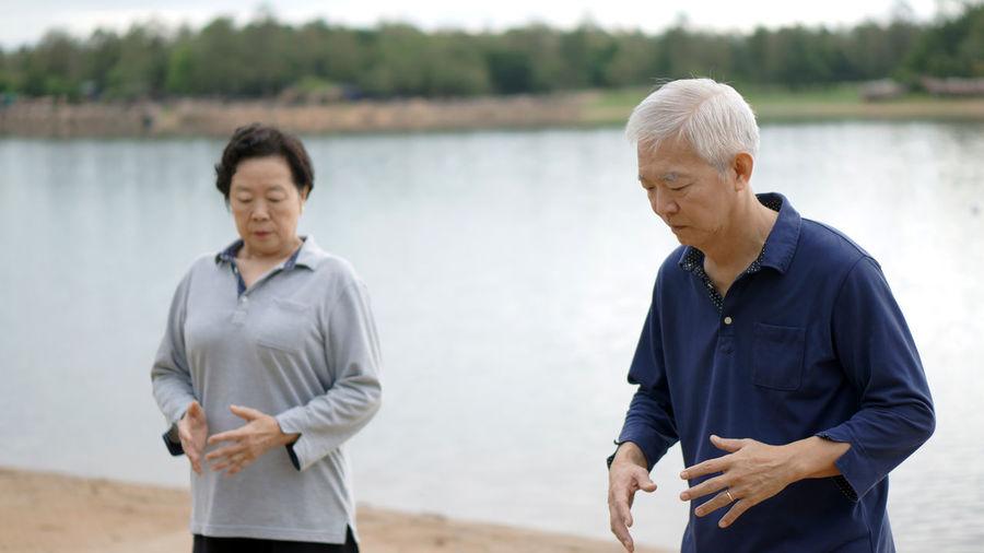 Active people doing tai chi at lakeshore
