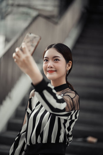 Beautiful woman taking selfie on mobile phone outdoors