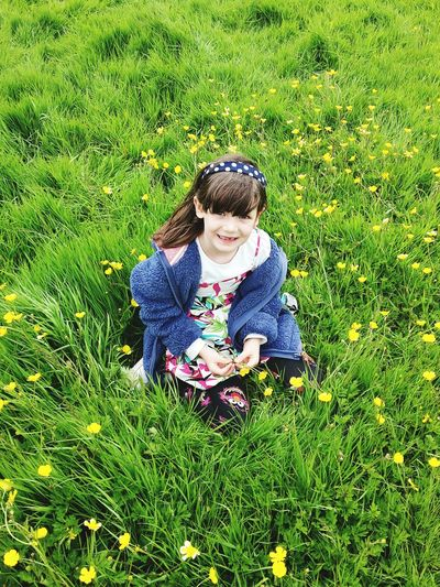 Portrait of cute girl lying on grassy field