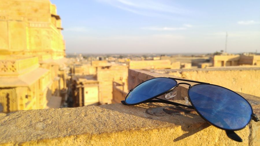 Close-Up Of Sunglasses On Retaining Wall
