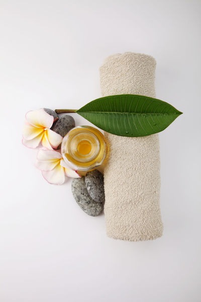 massage oil with frangipani and towel Aromatherapy Frangipani Hygiene Relaxing Alternative Medicine Beauty In Nature Close-up Directly Above Essential Oils Flower Flowering Plant Freshness Indoors  Massage Oil Nature No People Pebble Spa Still Life Stone Studio Shot Towel Treatment Wellbeing White Background