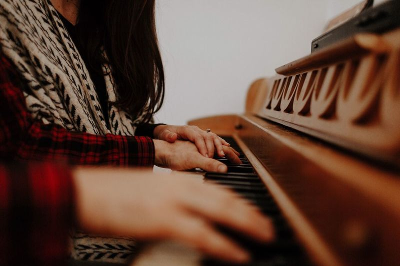 Close-Up Of Friends Playing Piano At Home