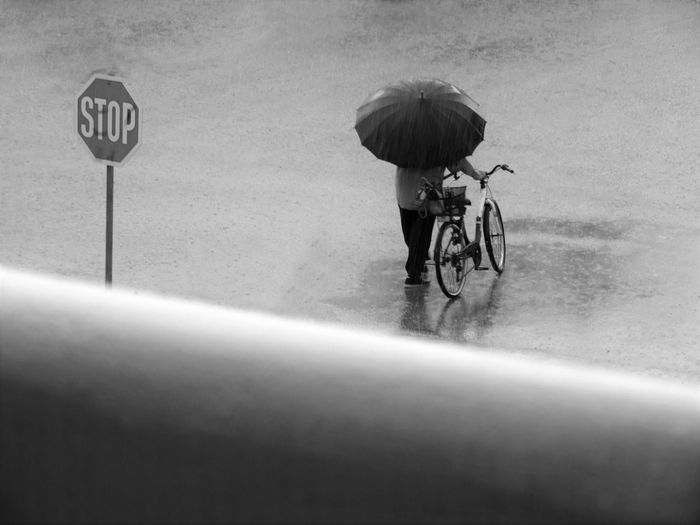Man with bicycle standing on road during rainy season