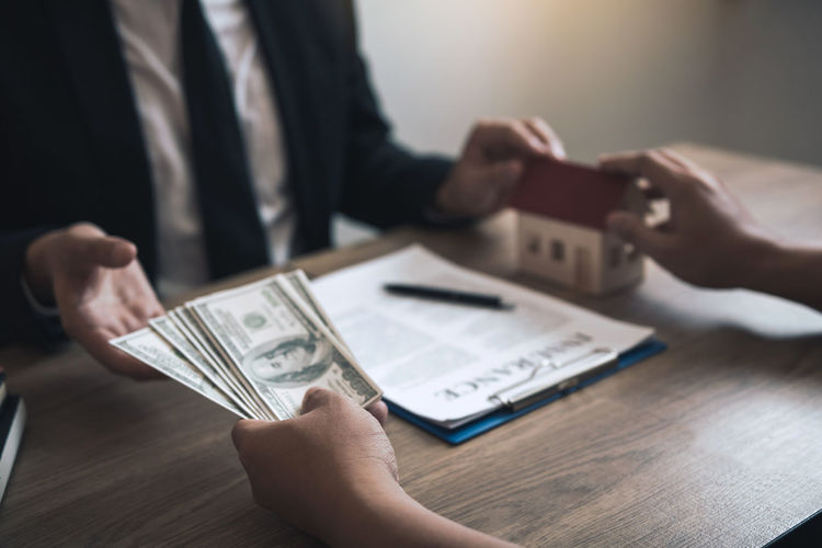 Cropped hand of customer giving paper currency to real estate agent on table
