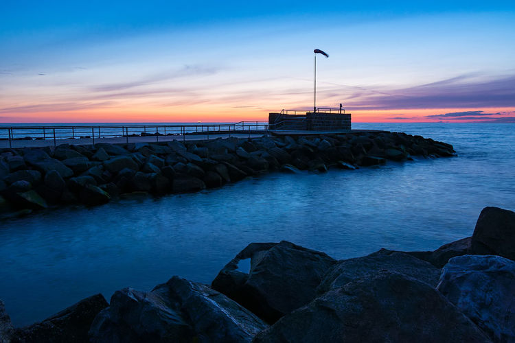 Mole at night in Warnemuende, Germany. Baltic Sea Relaxing Rostock Warnemünde Architecture Built Structure Coast Evening Groyne Horizon Over Water Mole Nature Night Outdoors Rock - Object Scenics Sea Shore Sky Tourism Tranquil Scene Travel Destinations Vacation Warnemuende Water