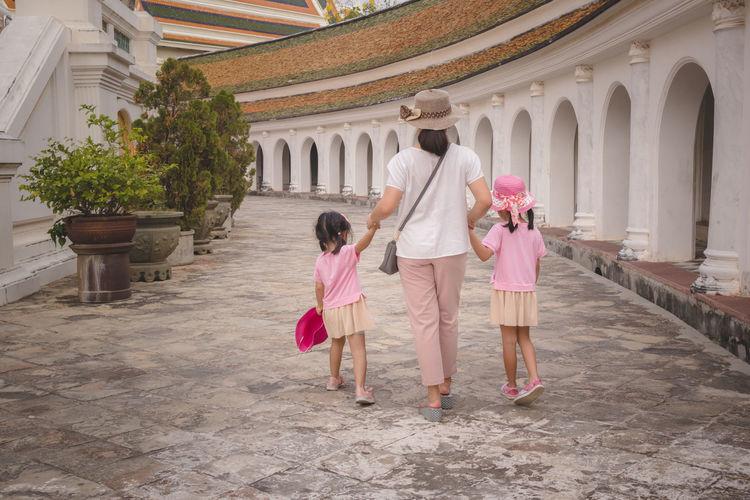 Rear view of women walking in temple outside building