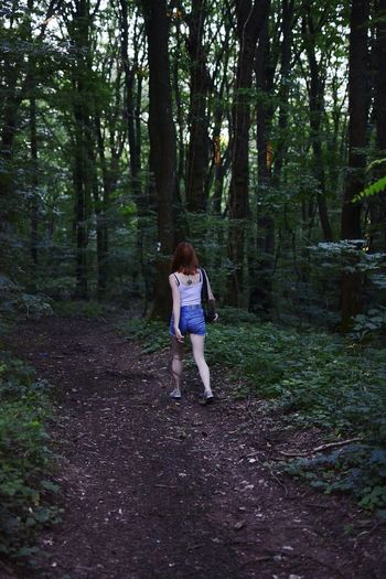 Full length of woman walking through the forest