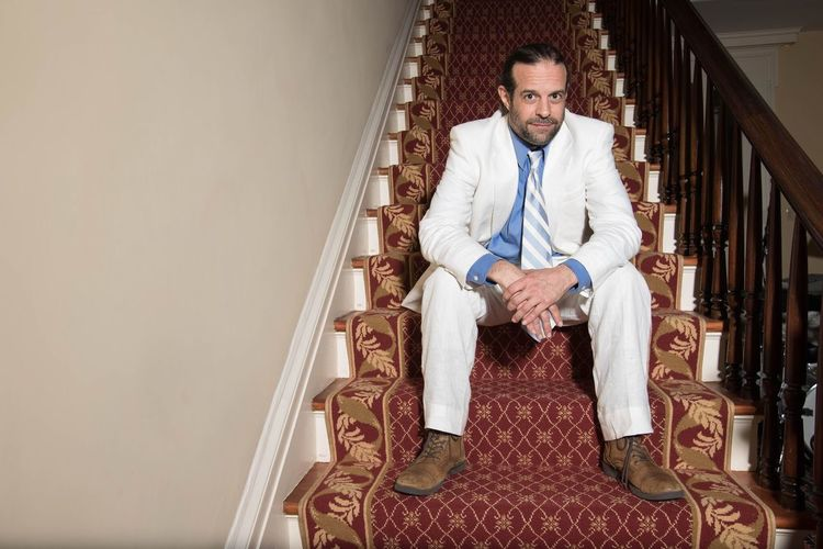 Portrait of smiling mature businessman sitting on staircase