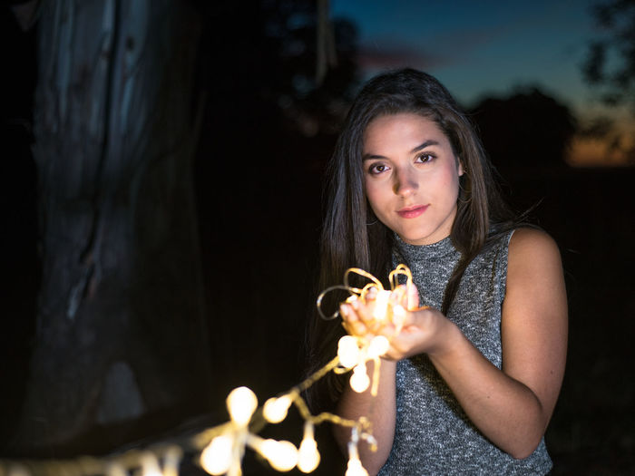 Portrait of beautiful young woman holding camera at night