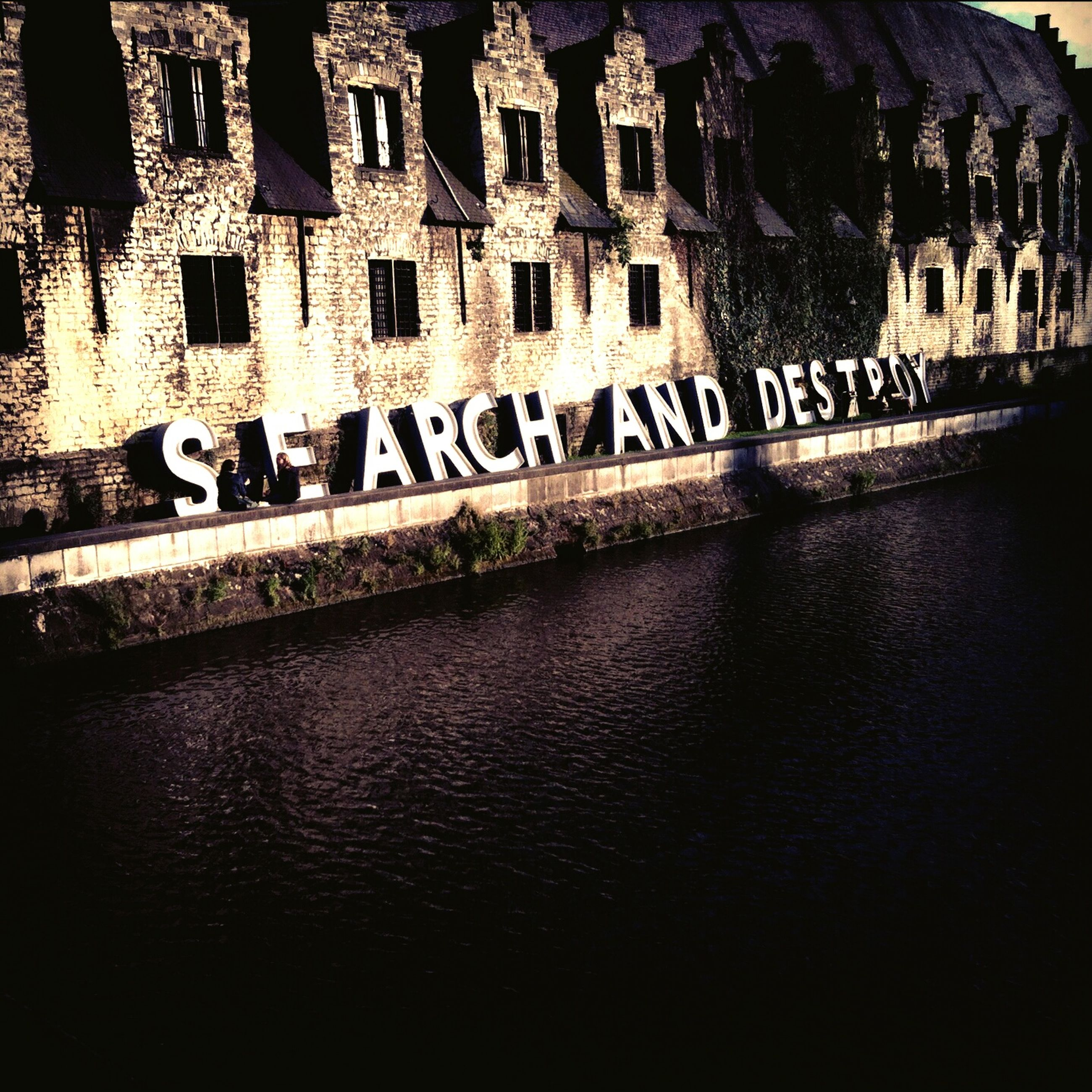 architecture, built structure, water, text, western script, building exterior, waterfront, history, reflection, famous place, communication, no people, river, travel destinations, outdoors, day, old, wall - building feature, building, the past