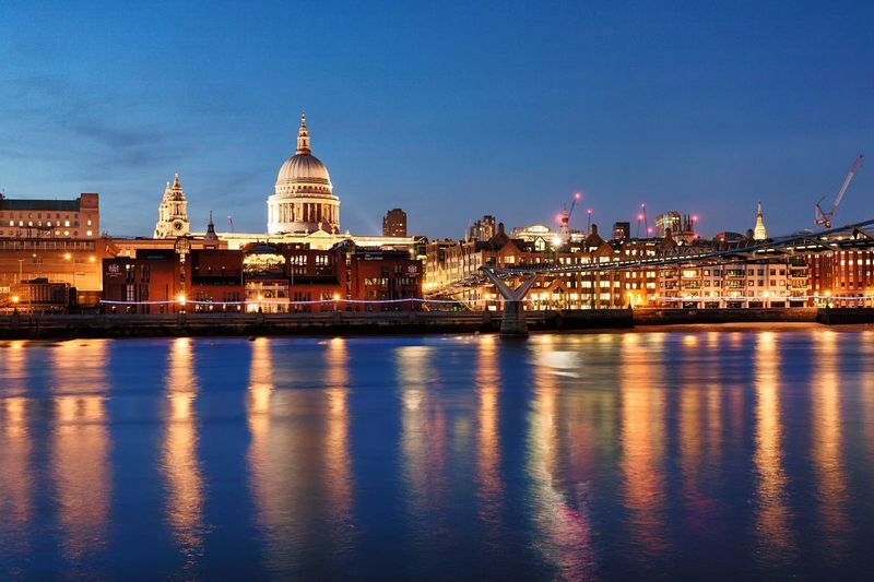 Millennium bridge over thames river by illuminated st paul cathedral against sky at dusk