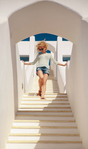 Low angle view of smiling young woman moving down building steps