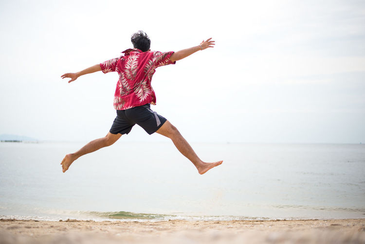 Rear view of man jumping on beach