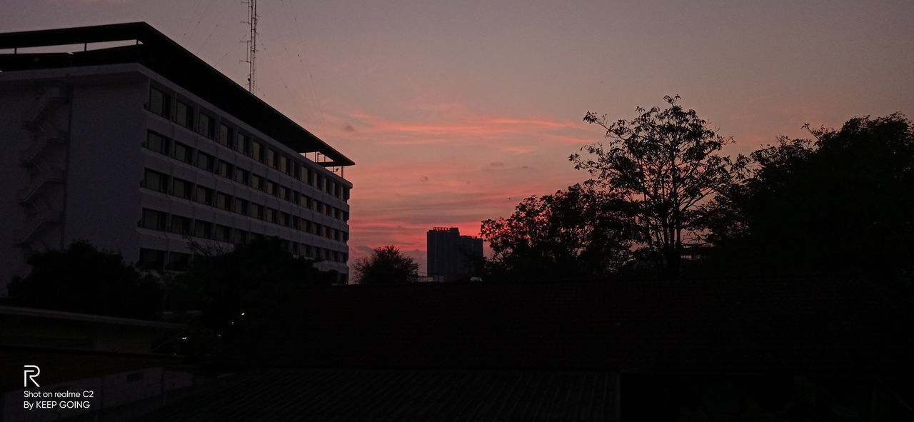 SILHOUETTE BUILDINGS AND TREES AGAINST SKY AT SUNSET