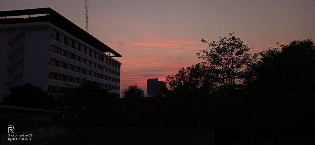 Silhouette trees and buildings against sky at sunset