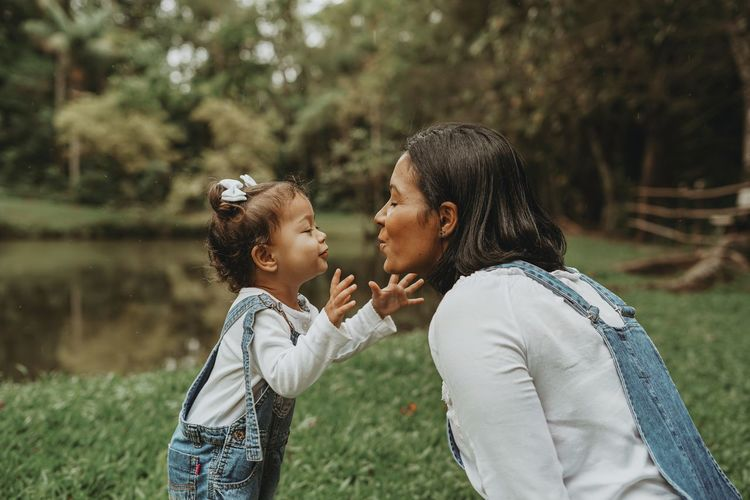 Side view of mother and daughter embracing at park