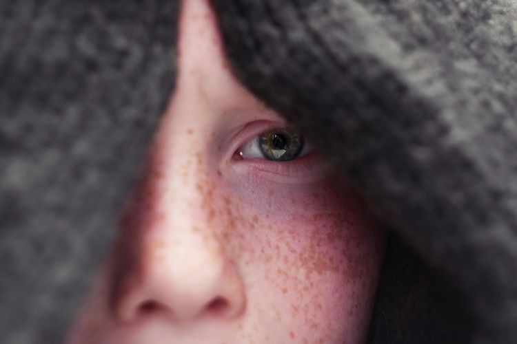 Close-up portrait of boy with freckles on face