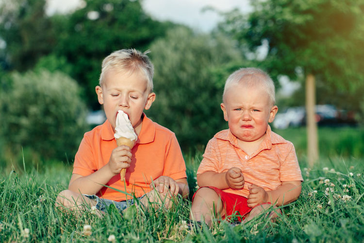 Toddler crying while brother eating ice cream on grass