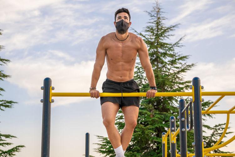 Full length of shirtless man sitting on railing