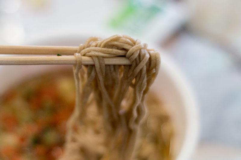 Close-up of eating soba noodles with cjopsticks