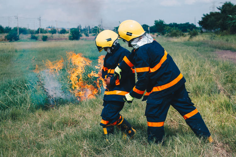 Firefighters by fire on field