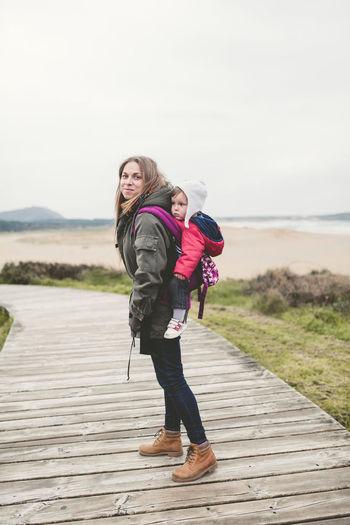 Full length portrait of mother carrying baby boy on boardwalk
