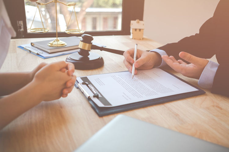 Midsection Of Lawyer Having Meeting With Client In Office