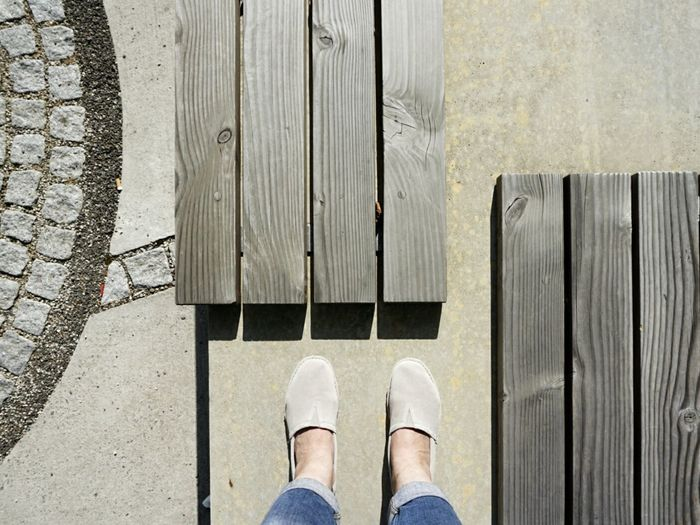 Low section of woman standing by planks