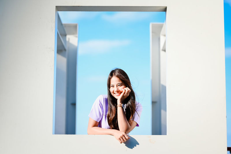 Portrait of smiling young woman standing against white wall
