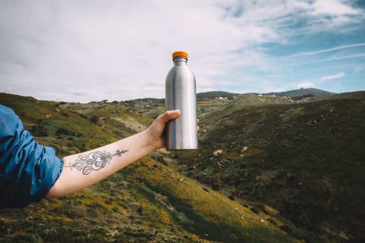Cropped image of hand holding bottle against mountains