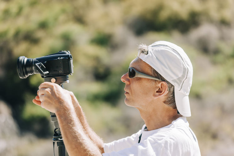 Side view of man using video camera