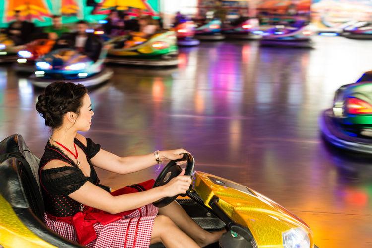 Woman enjoying in bumper car at amusement park