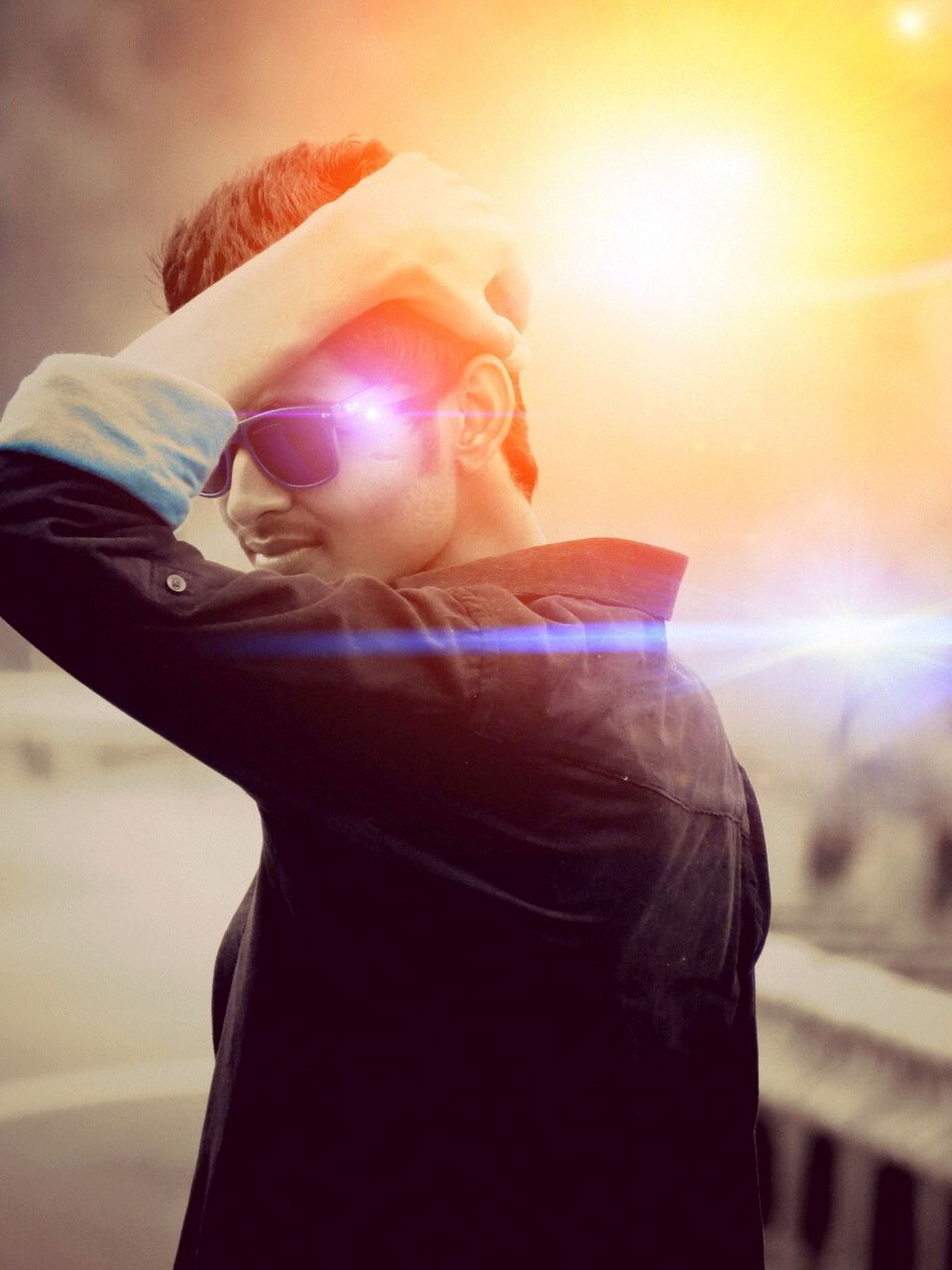 lifestyles, focus on foreground, leisure activity, person, casual clothing, headshot, young adult, front view, sunglasses, close-up, holding, sunlight, standing, waist up, hat, lens flare, three quarter length, side view
