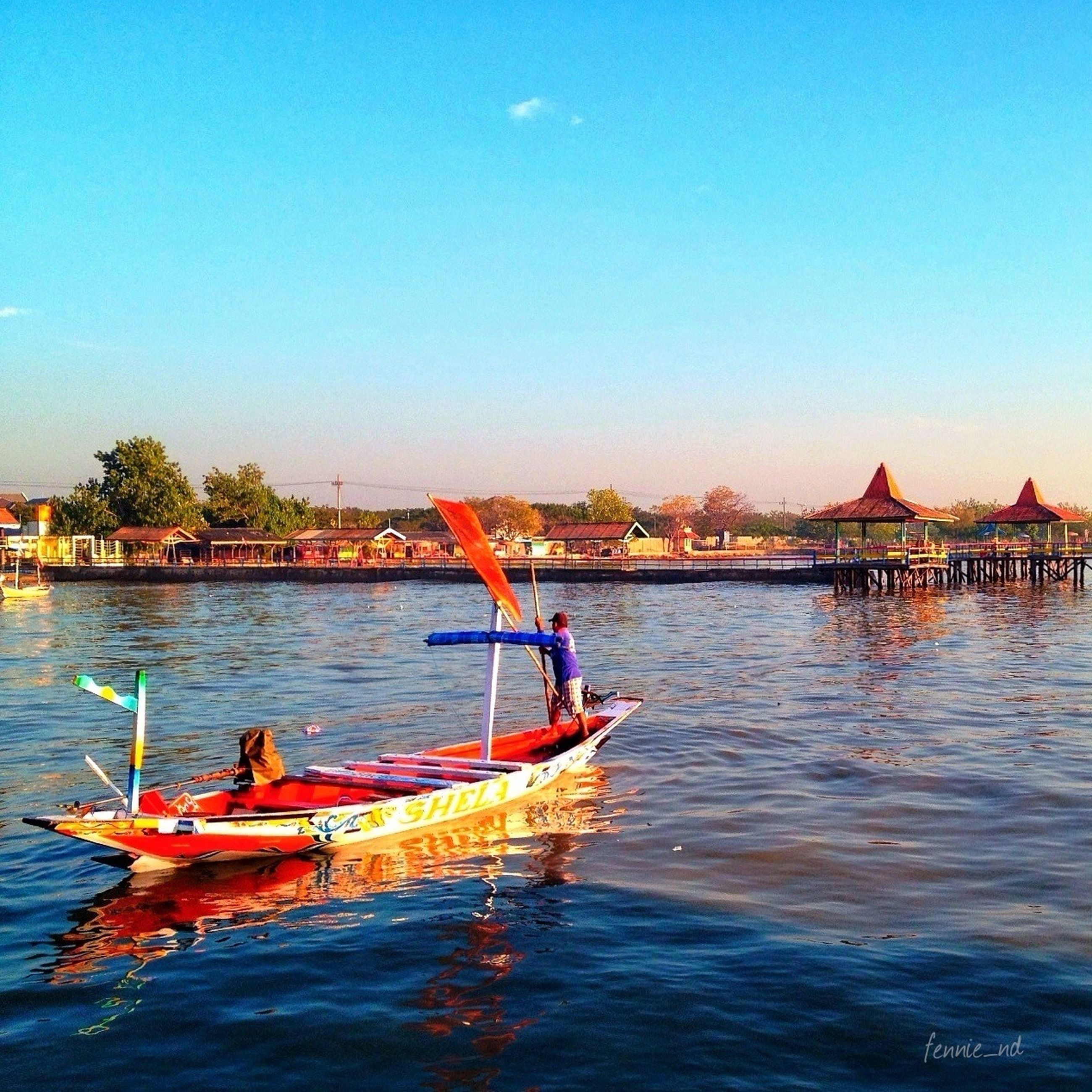 water, nautical vessel, transportation, clear sky, boat, mode of transport, waterfront, copy space, moored, built structure, blue, river, lake, architecture, building exterior, rippled, travel, nature, day, tranquility