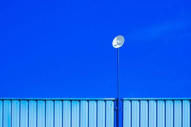 Low Angle View Of Satellite Dish On Corrugated Iron Against Blue Sky