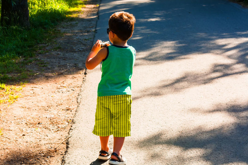 Full length of boy standing on road during sunny day