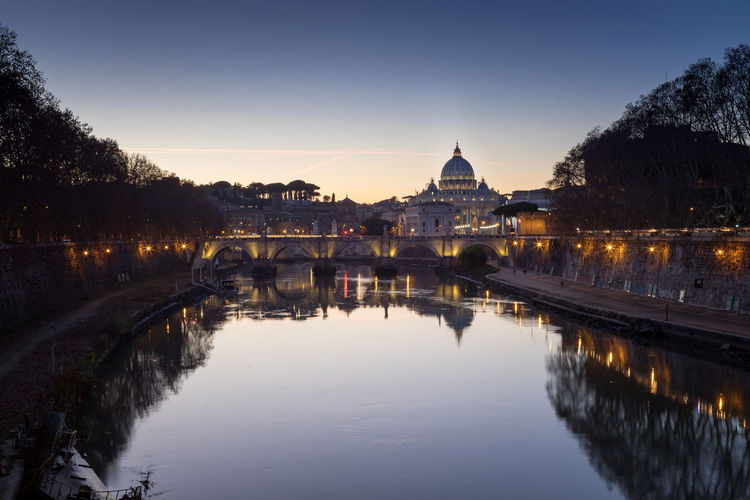 The bridge of sant'angelo, the tiber river and in the basilica of san pietro, at the sunset