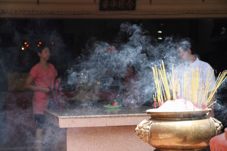 Presence? Buddhist Temple Burning Incense Cambodia Incense Incense Sticks Man Offerings Phnom Penh Place Of Worship Religion Smoke Spirituality Wat Phnom Cambodia Woman