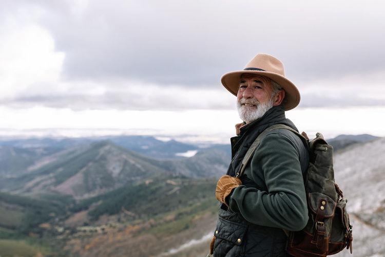 Man standing against mountain range against sky