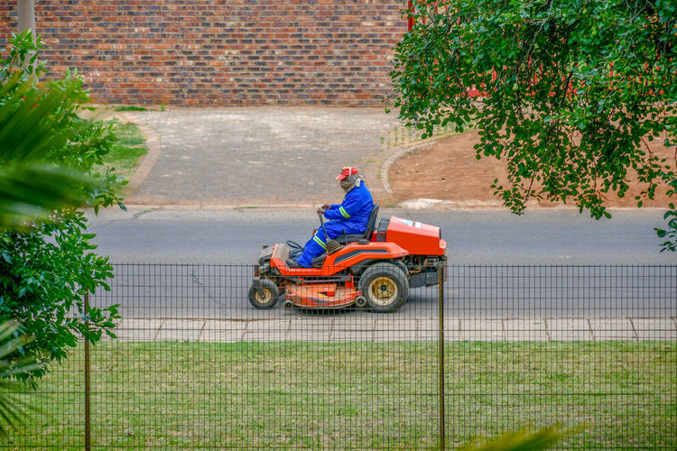 Man on a lawnmower. EyeEm Selects Architecture Flower Outside Yard Colors Portrait Pavement Environment Street Day Cap Adult Tractor Garden Sunlight Motion Driving Lawn Grass Engine Outdoors Road Mask Equipment One Person Man Tree Sitting Plant