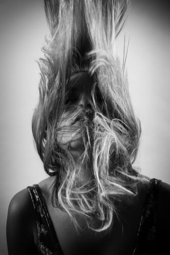 Close-up portrait of woman with hair against white background