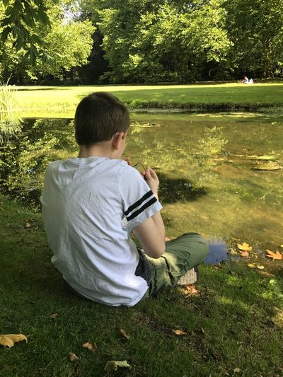 Rear view of boy sitting by lake at park