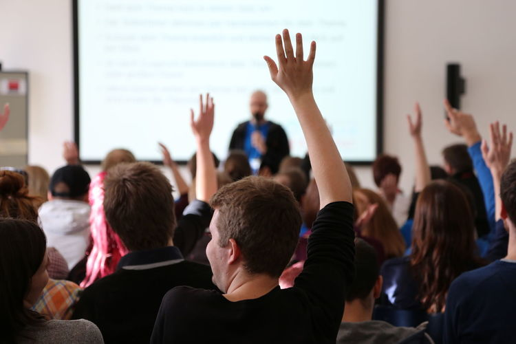 Students raising hands during seminar
