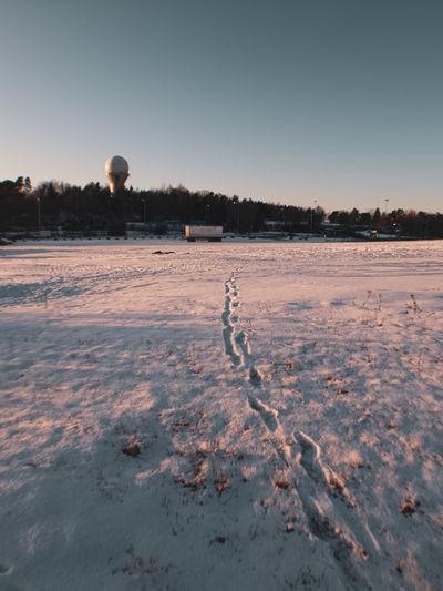 Footprints on snowy field in front of radar tower in stockholm