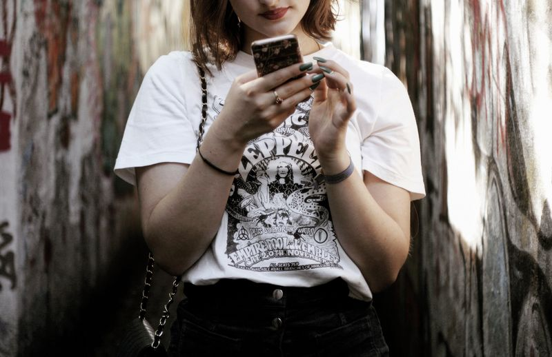 Full length of young woman using phone while standing on tree