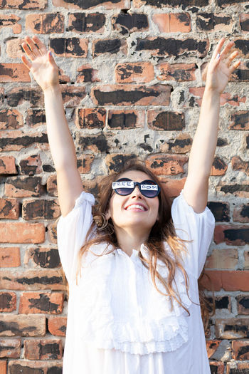 Smiling Woman Wearing Freedom Text Sunglasses Against Brick Wall